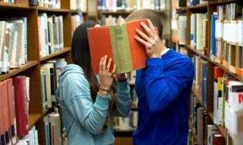 Young couple hiding behind book