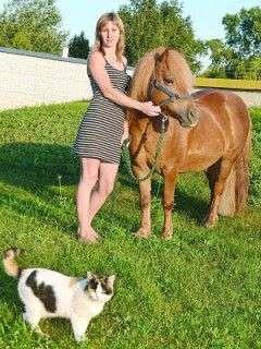 Людмила Редька стоїть із поні на території стаєнь. З чоловіком тримають 15 поні шетландської породи